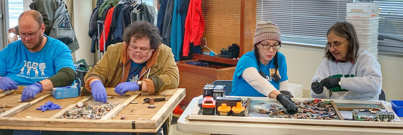 Volunteers sort batteries into categories