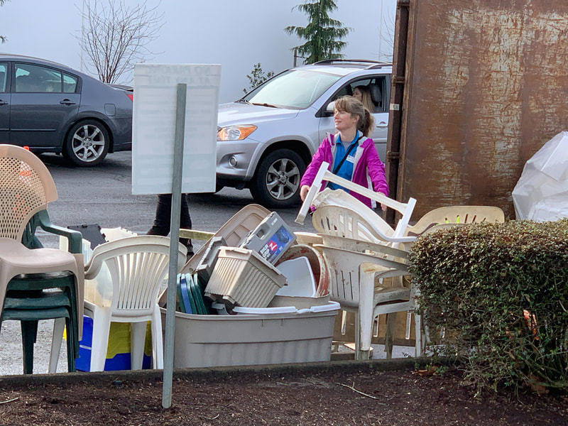 A woman carries lawn furniture to be recycled
