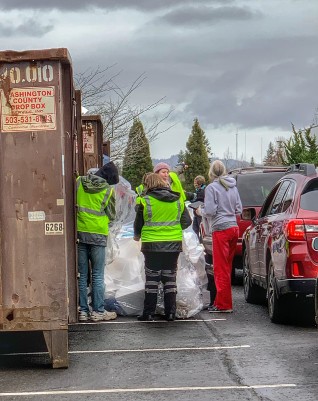 Volunteers collect styrofoam from guests in a line of cars