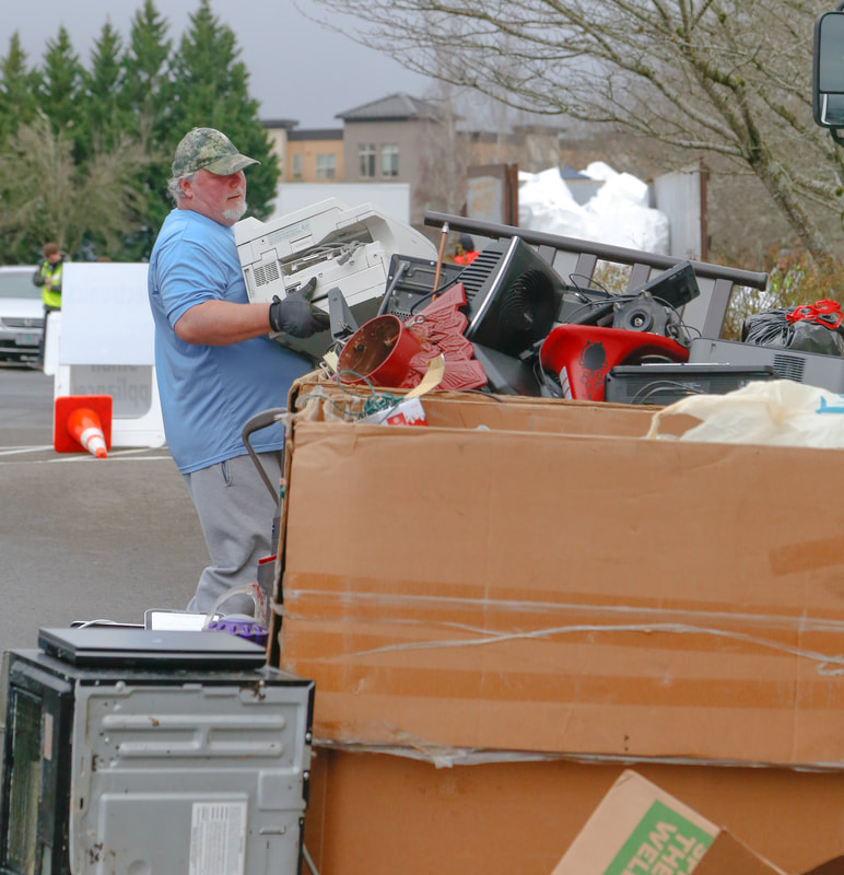 A man hauls electronics for recycling